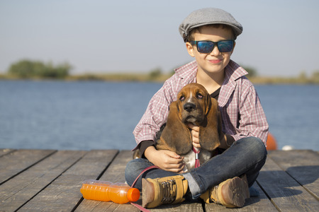 basset: Little sweet  boy with a hat and sunglasses sits by the river with his dog. They enjoy together on a beautiful sunny day. Child hugging his dog. Copy space Stock Photo