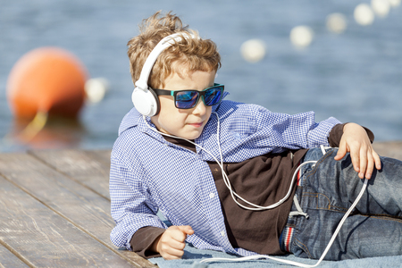 Portrait of a little sweet boy with sunglasses and headphones. He lies by the river, listens to music and enjoys a beautiful sunny day. He is a very modern and attractive boy. Copy space Stock Photo