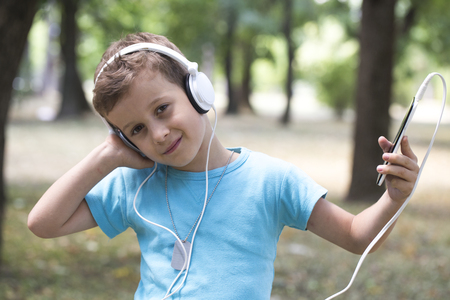 Portrait of a sweet little boy showing pleasure while listening to music. He holds a mobile phone in his hand and listens to his favorite music Stock Photo