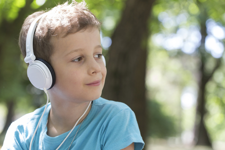 Close up portrait of a little sweet boy while listening to music and enjoying a beautiful sunny day. Copy space