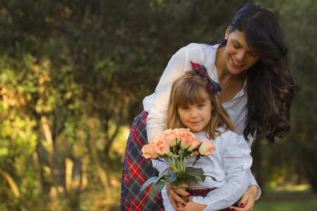 Young mother and daughter enjoying together outdoors in a beautiful autumn day. They are very happy. A little girl wants to give her mother a beautiful bouquet of flowers
