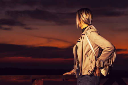 Young tourist girl with a backpack stands next to  to a wooden fence  at sunset and looks into the distance. Rest, relaxation, travel, vacation. High ISO Banco de Imagens - 88293286