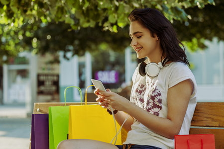 Young beautiful smiling girl, a teenager, resting on the bench after shopping. Next to her are full bags, things she bought. She holds a mobile phone in her hand and texting message. Stock Photo