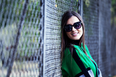 Portrait of young beautiful woman in urban background- old fence