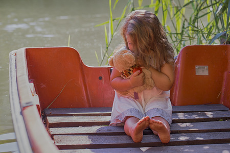 Little happy little girl playing  with her favorite toy while sitting in a boat on a lake and enjoying a beautiful sunny summer day