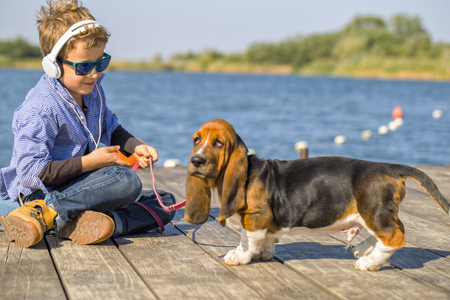 basset: Little cute boy is sitting by the river with his dog. They enjoy together on a beautiful sunny day. Boy with sunglasses listening to music via headphones. Growing up, love for animals - dogs, free time, travel, vacation. Copy space