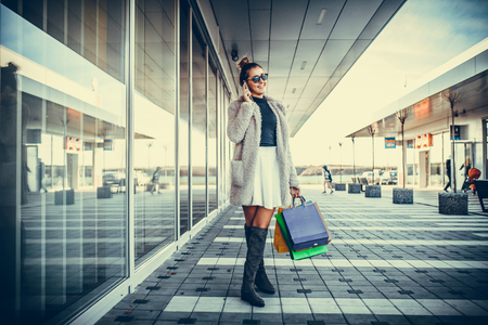 consumerism: Young happy woman standing in shopping mall talking over mobile phone