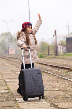 Little cute girl with suitcase standing on station waiting for a train