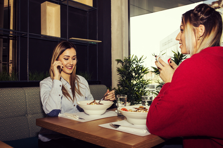 Female Friends Having Lunch Together At The Restaurant. Two young women using a mobile phone during lunch  in the modern interior of the restaurant .Woman phoning Stock Photo