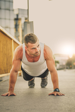 Portrait of a fitness man doing push ups outdoors. Fitness, sport, lifestyle concept