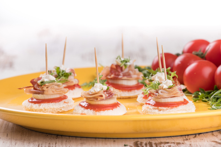 Delicious canapes with bacon and tomato on a wooden background