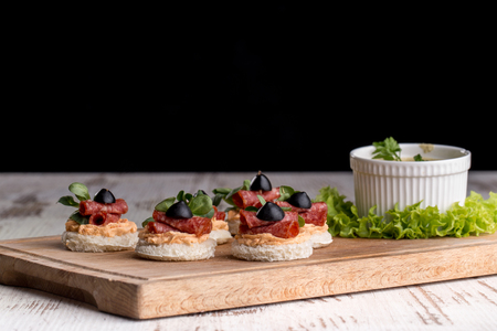 Delicious canapes with salami, olives and spices on a woody background