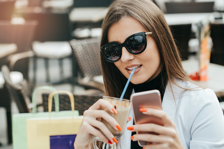 Fashion happy woman with sunglasses using a smartphone in a coffee shop and holding a cup ready to drink. Close up