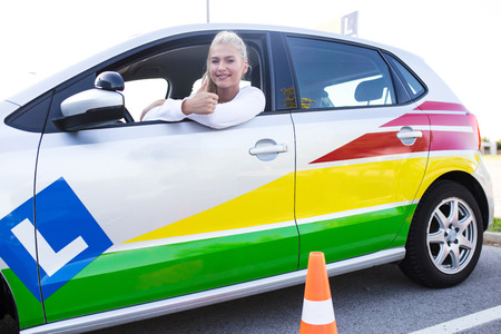 Fahrschule. Junge glückliche Frau, die in einem Auto sitzt. Fahrer sutdent zeigt stolz Daumen hoch. Freier Platz für Text. Speicherplatz kopieren.