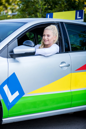 Driving school. Young smiling woman - student sitting in a car. Free space for text. Copy space. Stock Photo