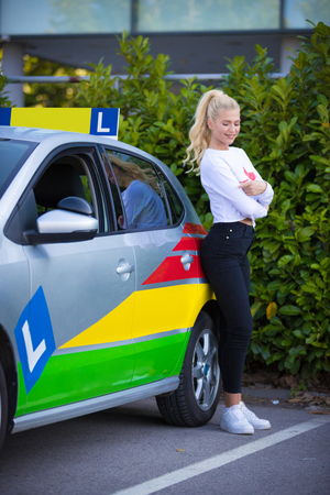 Driving school. Young happy woman or drinving student standing next to a car. Free space for text. Copy space.
