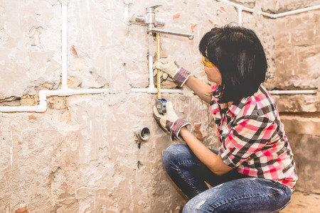 Clever woman repairing her bathroom sink pipe with  positive attitude. Using measuring tape ruler.