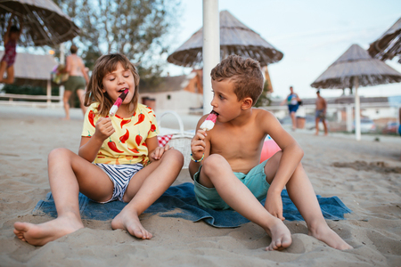 Happy positive children sitting on the sandy beach and eating ice cream. People, children, friends and friendship concept