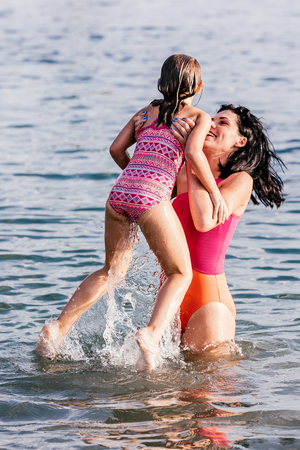 Little cute girl playing with mother in the water. Happy mother holding daughter in her arms. Happy family. Vacation, travel concept Stockfoto