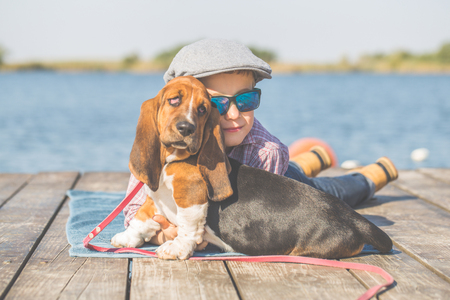Little cute boy lying by the river with his dog. They enjoy together on a beautiful sunny day. Boy hugging his puppy. Growing up, love for animals - dogs, free time, travel, vacation. Copy space 写真素材