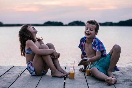Portret van positieve kinderen die samen met smartphone spelen op houten pier. Kinderen lachen, genieten van de prachtige zonsondergang