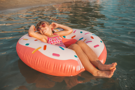 Happy little girl lying with inflatable ring in water on hot summer day. Kids learn to swim. Child water toys Stockfoto