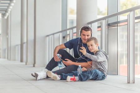 Little boy and his father taking a break and listening to the music together in a sports center. Father and son spend time together and lead a healthy lifestyle.  Making selfie photo