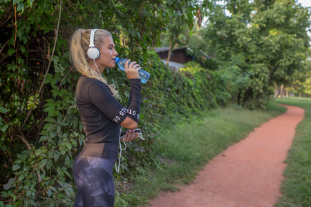 Refreshing after workout.Young sporty woman taking a break after training, drinking water and listening to music via headphones