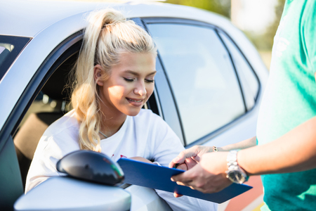 Driving school. Young woman or driving student on a driving test with her instructor. Learning to drive a car. Instructor of driving school giving exam while standing next to the car