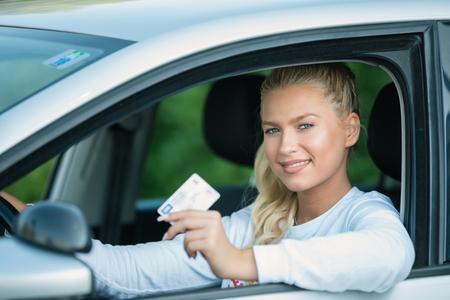 Scuola guida. Attraente giovane donna che mostra con orgoglio la sua patente di guida e sorridente nel veicolo. Spazio libero per il testo. Copia spazio.
