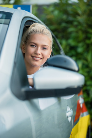 Young woman driving student sitting in a car. Portrait of a beautiful woman in a car, looking out of the window and smiling. Driving school