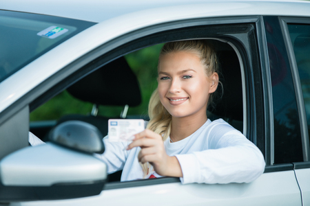 Szkoła jazdy. Atrakcyjna młoda kobieta dumnie pokazując jej prawo jazdy. Wolne miejsce na tekst. Skopiuj miejsce.