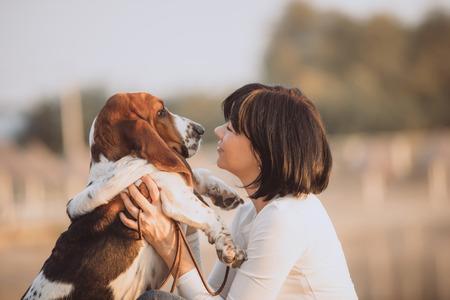 Close-up portret van mooie jonge vrouw spelen met haar hond Basset Hound door de rivier. Liefde tussen mens en hond