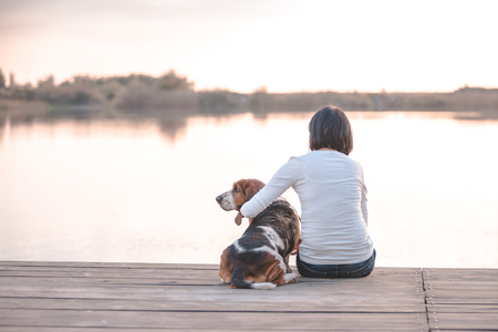 Pretty young woman hugging her dog Basset Hound on the wooden dock on the river