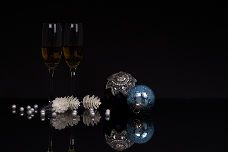 Two wine glasses with champagne and Christmas ornaments on a black background with reflection. Copy space. Merry Christmas and Happy New Year, background