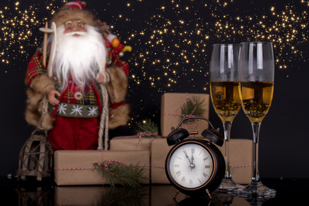 Two wine glasses with champagne, Santa Claus, clock and christmas gifts on a black background with reflection. Copy space. Merry Christmas and Happy New Year, background