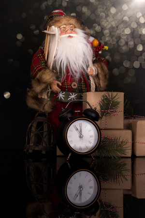 Santa Claus, clock and christmas gifts on a black background with reflection. Copy space. Merry Christmas and Happy New Year, background
