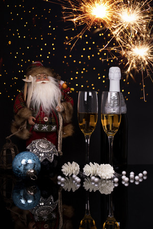 Two wine glasses with champagne, Santa Claus, sparklers and Christmas ornaments on a black background with reflection. Copy space. Merry Christmas and Happy New Year, background
