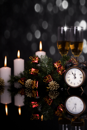 Two wine glasses with champagne, clock and Christmas ornaments on a black background with reflection. Copy space. Merry Christmas and Happy New Year, background