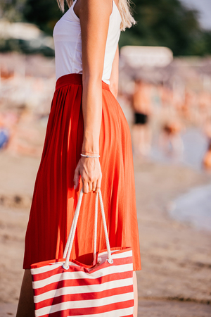 Pretty young woman with bag on the beach on a hot summer day