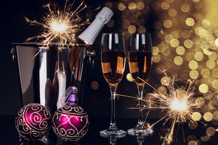 Two wine glasses with champagne, bottle, sparklers and Christmas ornaments on a black background. Copy space. Merry Christmas and Happy New Year, background 스톡 콘텐츠