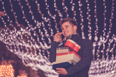Handsome man talking on the mobile phone and holding presents at night in decorated city street. - Image