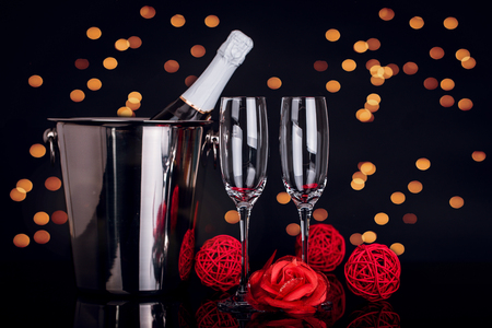 Champagne bottle in bucket, two wine glasses and  red rose on black background with lights in the background. Love, Valentines day concept