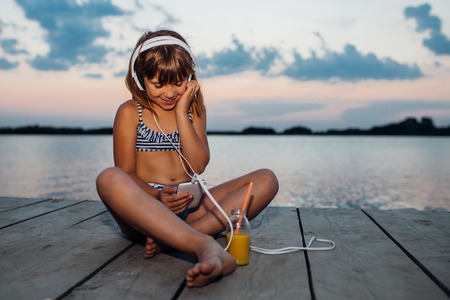 Portrait of a sweet little girl with headphones while sitting on wooden pier by the sea and listening to music on her smartphone. Child enjoying the beautiful sunset
