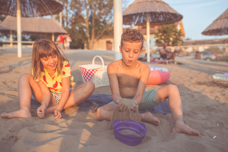Happy positive children sitting on a towel on the beach and playing with sand Archivio Fotografico