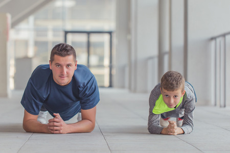 Little boy and his farher doing push ups exercises together at a sports center. Father and son spend time together and lead a healthy lifestyle.Working Out Together. Fitness Day. Sporty Family Concept. Imagens