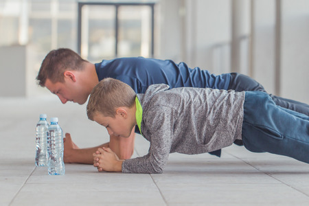 Little boy and his father exercising together at a sports center. Father and son spend time together and lead a healthy lifestyle.Working Out Together. Fitness Day. Sporty Family Concept. Active Lifestyle Imagens