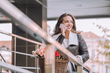 Beautiful young smiling woman with shopping bags and bicycle talking on the mobile phone.