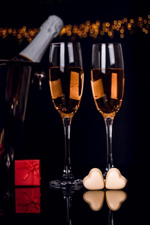 Two wine glasses, gift in a box and two heart-shaped chocolates on black background with golden lights . Love, Valentines day concept Stock Photo