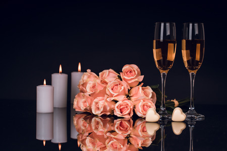 Two glasses of champagne, roses, candles and two heart shape chocolates on black background with lights in the background. Love, Valentines day concept